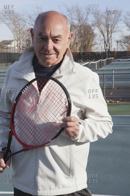 Smiling Hispanic man holding tennis racket