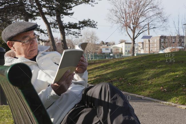 Hispanic man sitting on park bench reading book