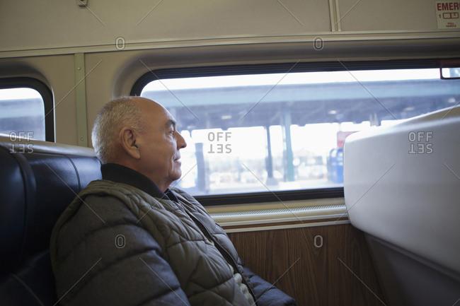 Hispanic man sitting on train