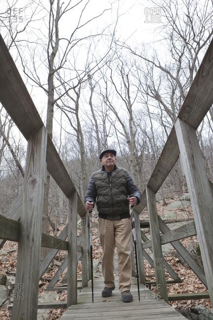 Hispanic man walking on footbridge using walking sticks
