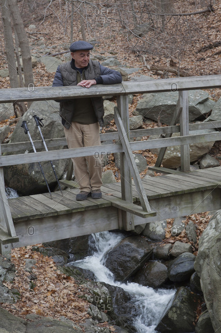 Hispanic man relaxing on footbridge
