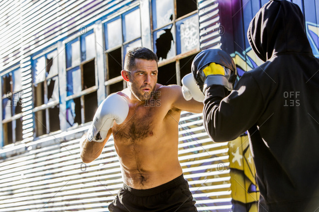 Caucasian boxer sparring with trainer