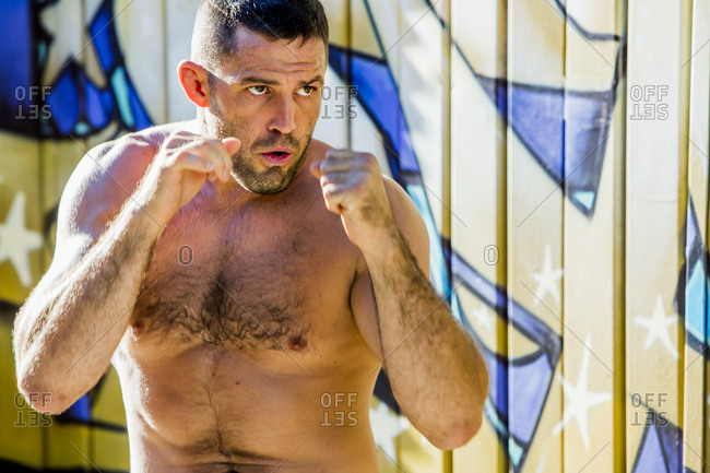 Caucasian man with bare chest boxing
