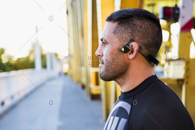 Pensive Caucasian man wearing modern headphones on bridge
