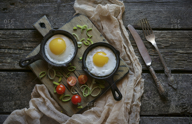 Fried eggs in cast iron pans on cutting board