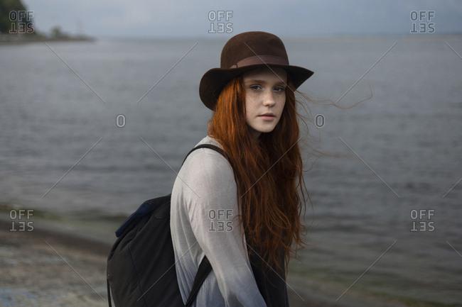 Serious Caucasian woman standing near ocean