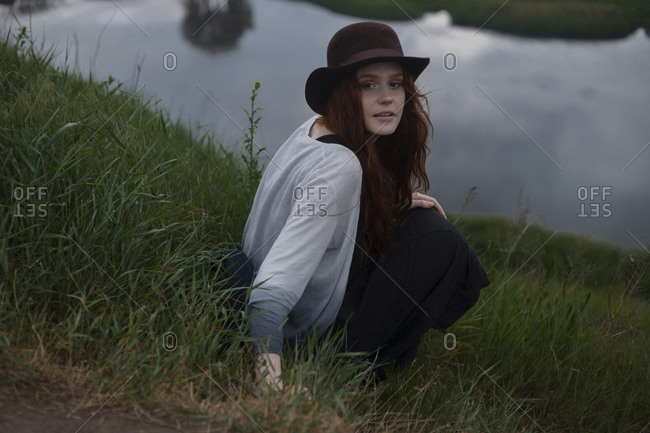 Serious Caucasian woman sitting on hill near lake