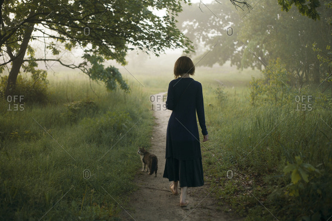 Woman and cat walking on path in fog
