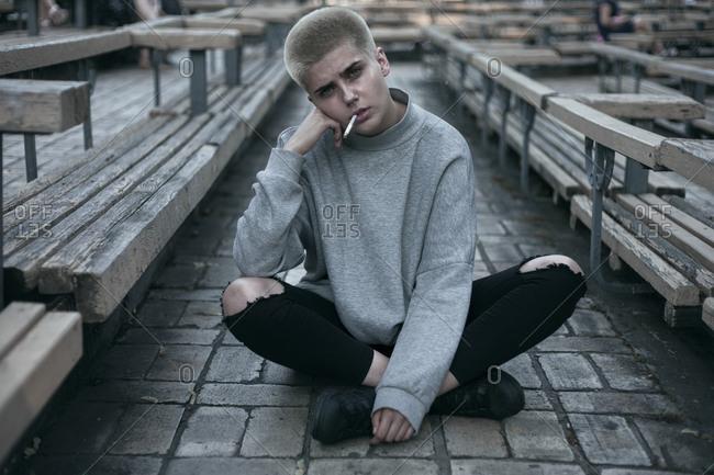 Punk Caucasian woman sitting on cobblestones smoking cigarette