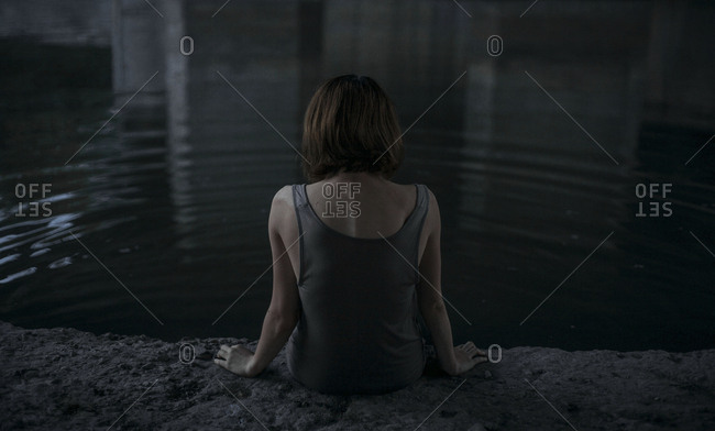 Caucasian woman sitting at edge of water