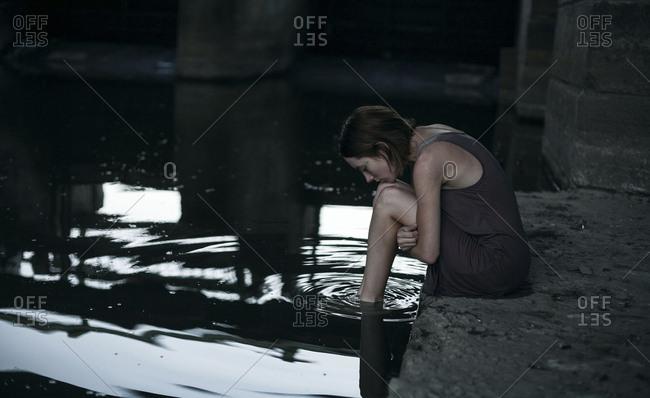 Pensive Caucasian woman sitting at edge of water