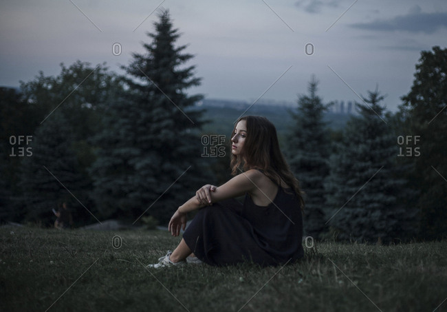 Pensive Caucasian woman sitting in field of grass