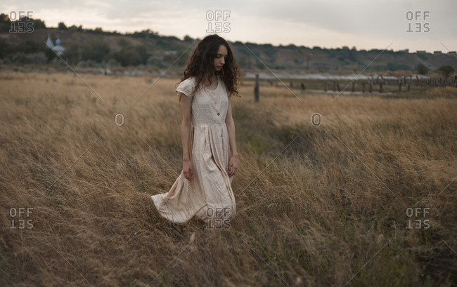 Serious Caucasian woman walking in field