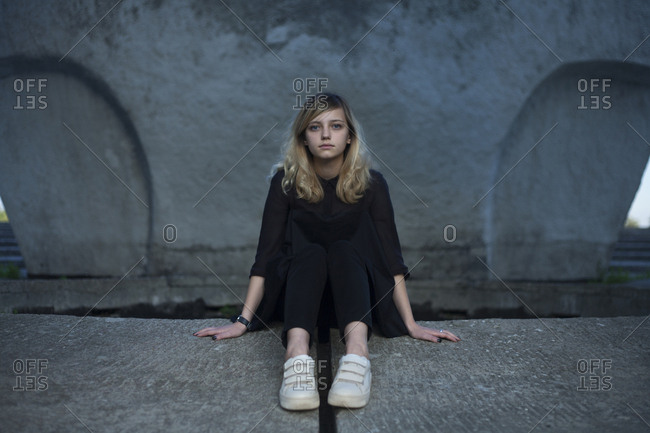 Portrait of serious Caucasian woman sitting on concrete