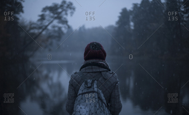 Woman carrying backpack standing near still lake