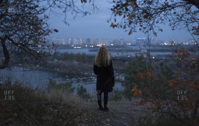 Pensive Caucasian woman standing near urban waterfront at night