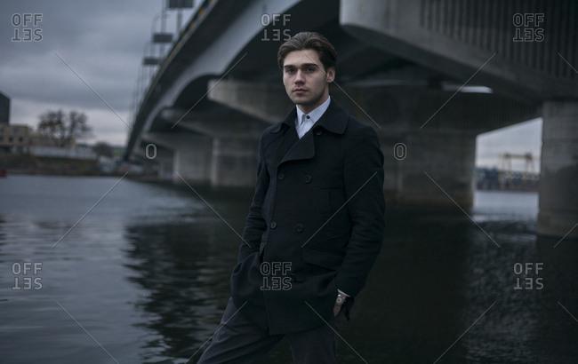 Portrait of serious Caucasian man standing under bridge