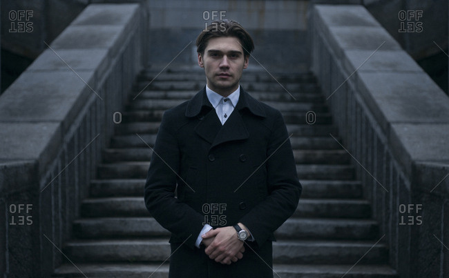 Portrait of serious Caucasian man standing near staircase