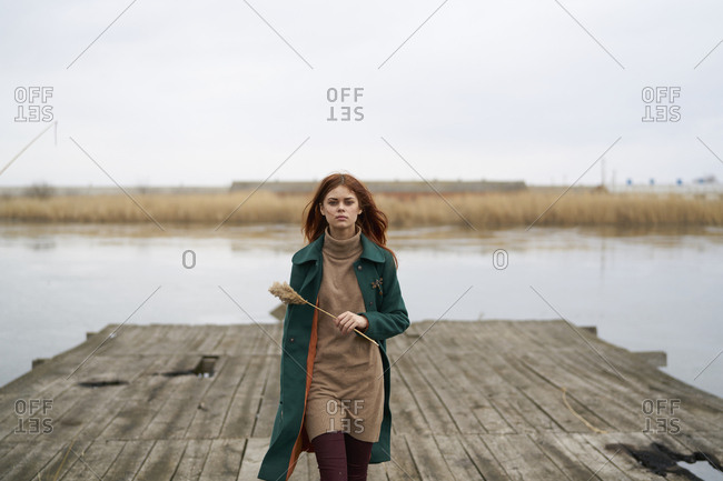 Serious Caucasian woman walking on dock holding stalk of grass