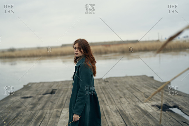 Serious Caucasian woman standing on dock