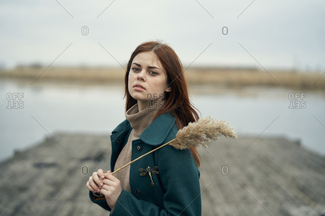 Serious Caucasian woman standing on dock holding stalk of grass