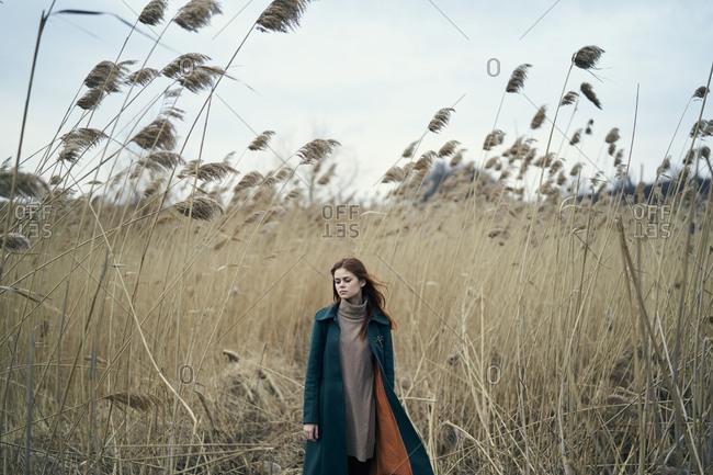Pensive Caucasian woman standing in field