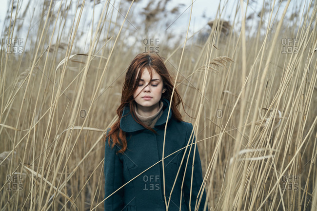 Caucasian woman standing in field with eyes closed