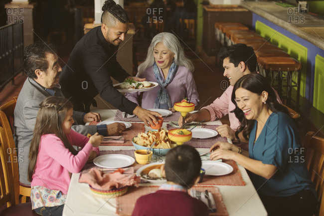 Waiter serving food to family in restaurant