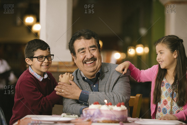 Hispanic grandchildren celebrating birthday of grandfather in restaurant