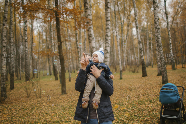 Middle Eastern father holding baby son and pointing in autumn