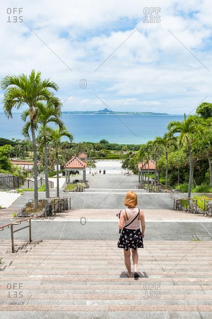 Woman walking down steps by sea