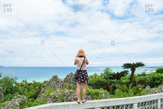 Woman on wall looking at sea
