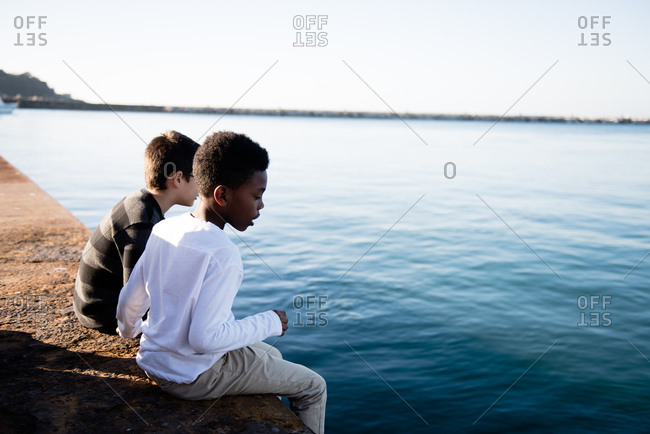 Boys sitting by sea in Procida, Italy