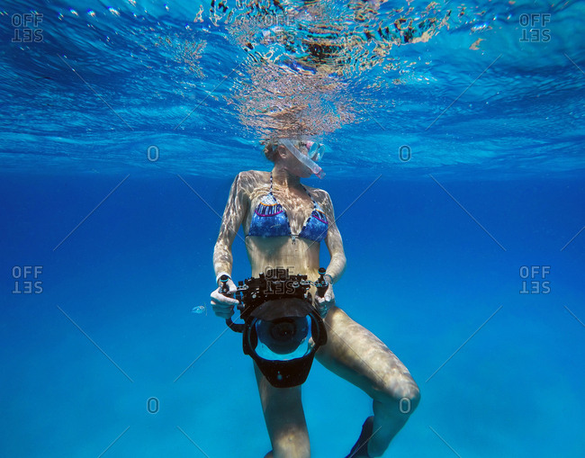 Woman holding a camera underwater