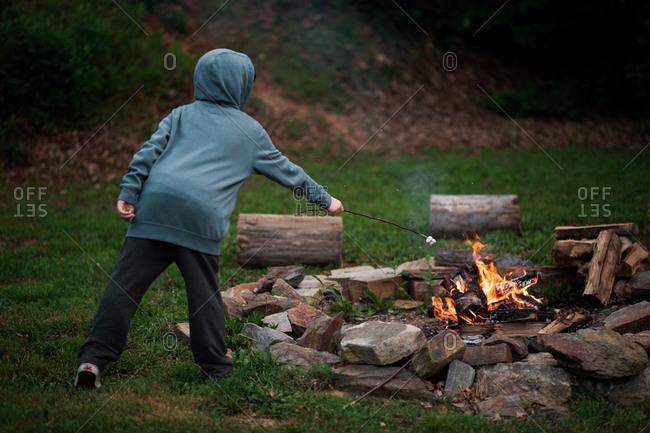 Kid roasting marshmallow in campfire