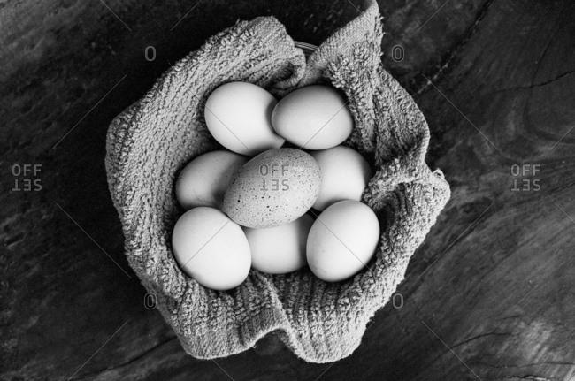 Fresh eggs in cloth on table