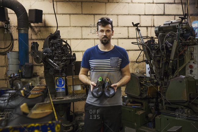 Man standing in a shoemaker's workshop, holding a pair of brown leather laced cycling shoes