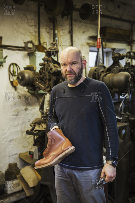 Man standing in a shoemaker's workshop, holding a pair of brown leather ankle boots