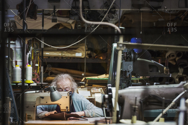 A senior grey haired woman worker sitting at a leather stitching machine in a shoemaker's workshop