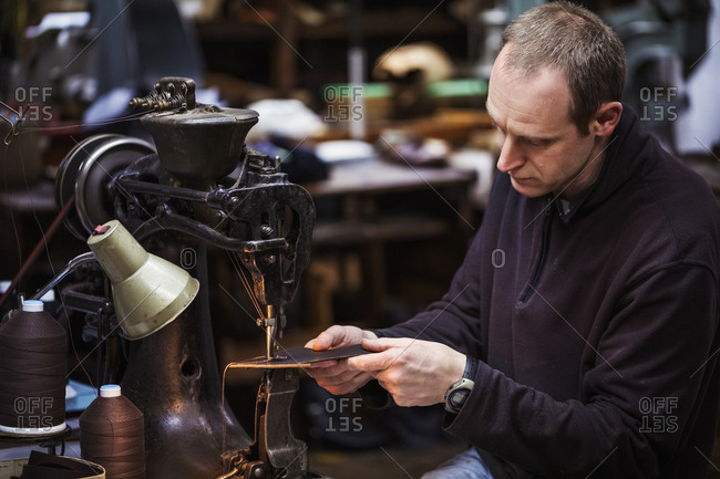 Man sitting at a large leather stitching machine in a shoemaker's workshop