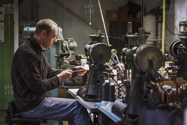 Man sitting at a sewing machine in a shoemaker's workshop