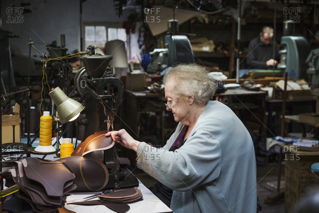 A grey haired senior worker, a woman sitting at a sewing machine in a shoemaker's workshop