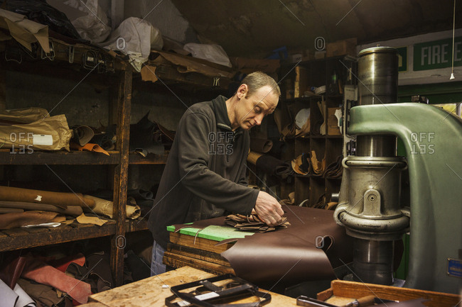 Man standing in a shoemaker's workshop, cutting brown leather