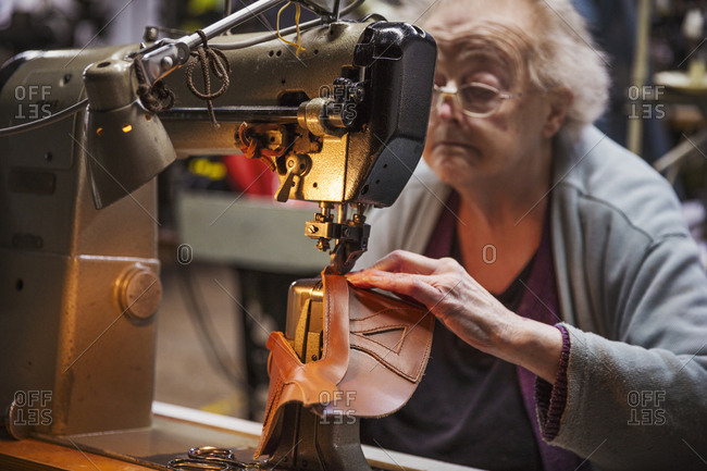 Older woman sitting at a sewing machine in a shoemaker's workshop
