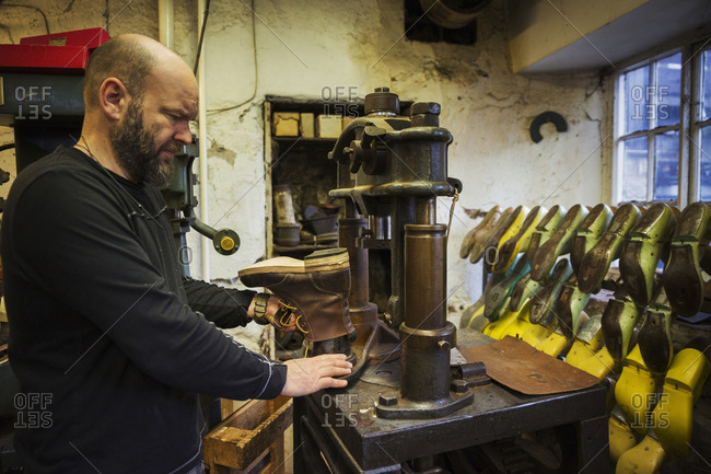 Man standing in a shoemaker's workshop, using a machine to make a leather ankle boot