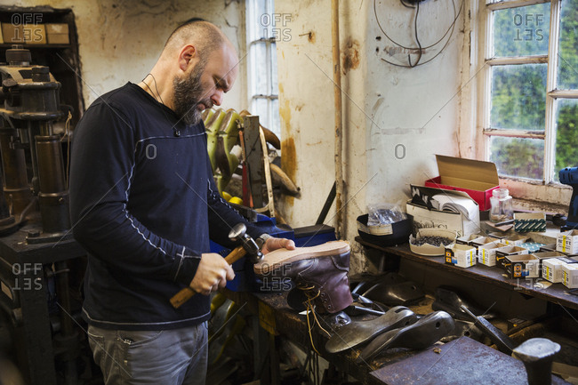 Man standing in a shoemaker's workshop by a window, using a hammer on the soles of a work boot