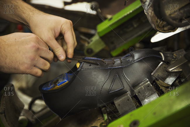 Close up of man standing in a shoemaker's workshop, tying the laces of a leather cycling shoe