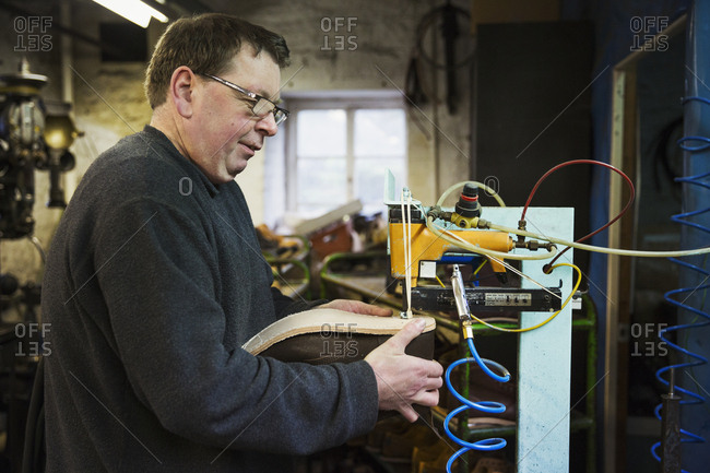Man standing in a shoemaker's workshop, using a machine to sew a sole onto a shoe