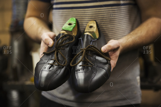 Close up of man standing in a shoemaker's workshop, holding a pair of handmade cycling shoes