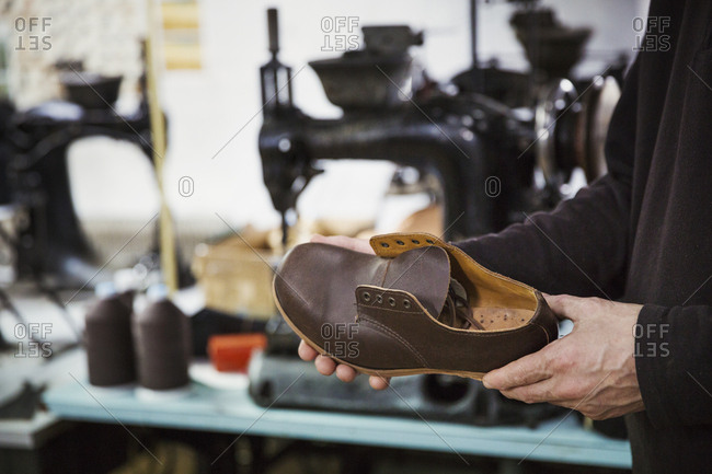 Man standing in a shoemaker's workshop, holding brown leather shoe